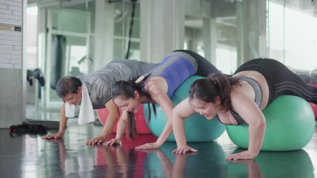 Group people doing pilates by fitness ball.