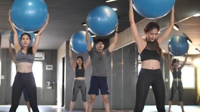 persone di gruppo che fanno yoga con palla fitness - metodo pilates video stock e b–roll