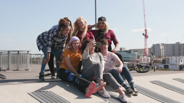Group portrait of young female BMX riders hanging out together taking a selfie