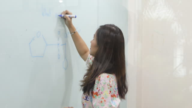 Group Students raise their hands to ask a friend questions for teaching at whiteboard in classroom - vídeo