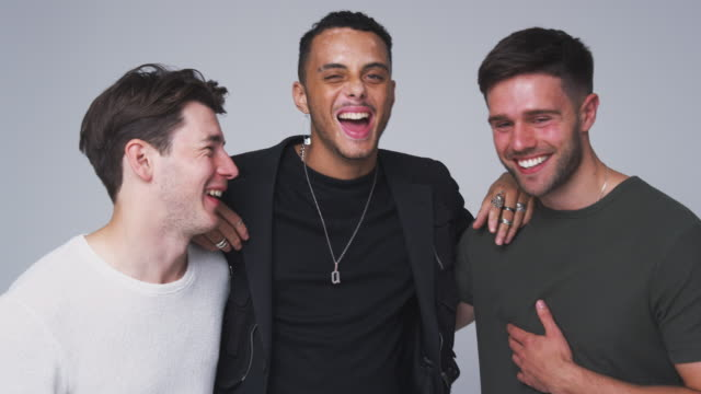 group studio portrait of multi-cultural male friends smiling into camera together in slow motion - tre persone video stock e b–roll
