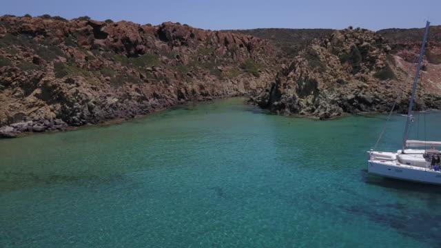 group swims near anchored sailboat in remote island cove - 40 49 lat filmów i materiałów b-roll