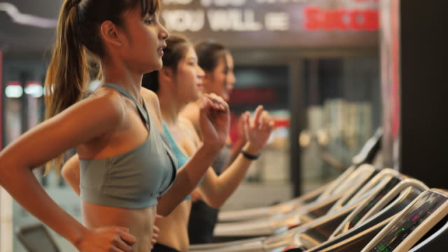 vídeos de stock e filmes b-roll de group young beautiful woman asian running on a treadmill at gym. fitness and healthy lifestyle concept. side view of girl in sportswear jogging exercise. slow motion - peso equipamento para exercícios