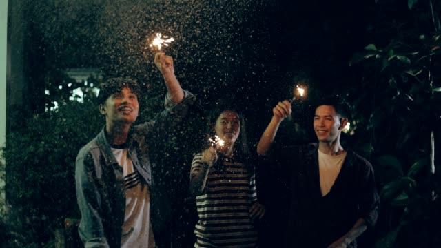 stockvideo's en b-roll-footage met youngs groep met wonderkaarsen dansen, slow motion - oost aziatische cultuur