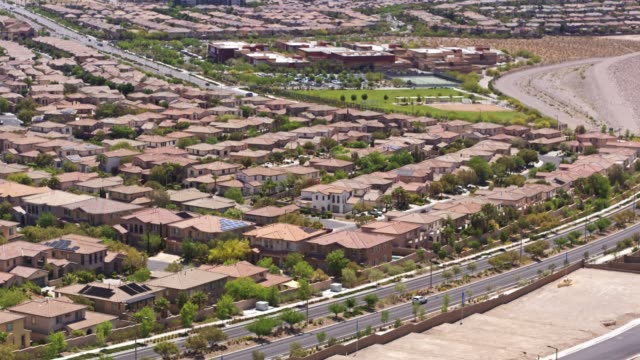 growing suburbs on the edge of las vegas - drone shot - città diffusa video stock e b–roll