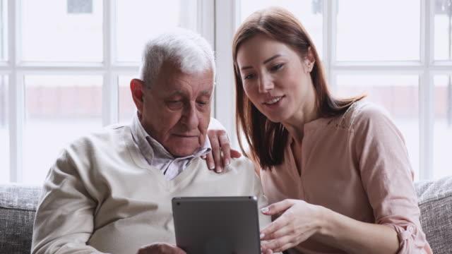Grown up granddaughter teaching older grandpa using digital tablet