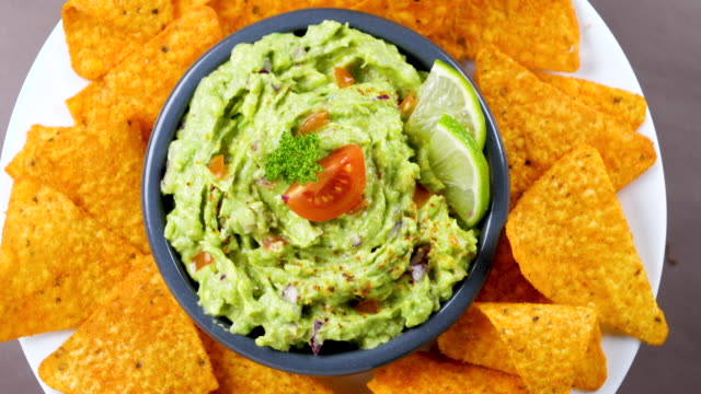 guacamole with tortilla chips- top view - immergere video stock e b–roll