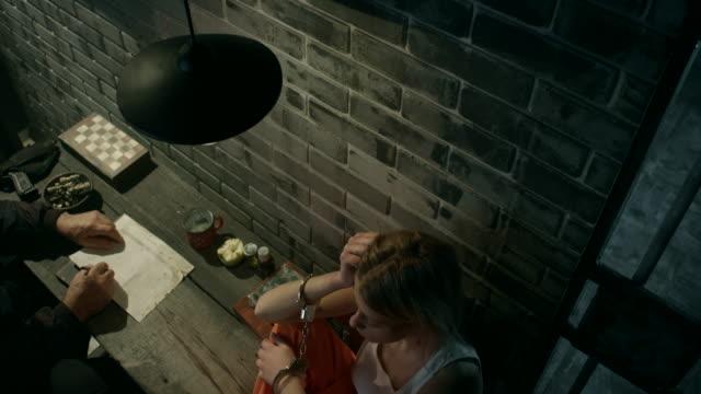 Guard interrogating women in jail Senior guard interrogating young women in jail legal trial stock videos & royalty-free footage