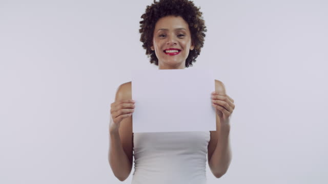 Guess what I found... 4k video footage of a beautiful young woman holding a blank sign against a grey studio background representing stock videos & royalty-free footage