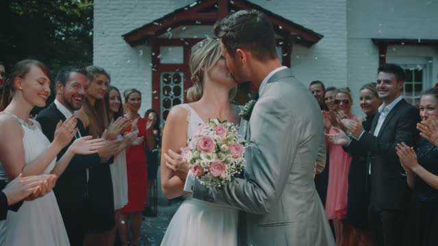 guests clapping for married couple kissing at event - young couple wedding friends video stock e b–roll