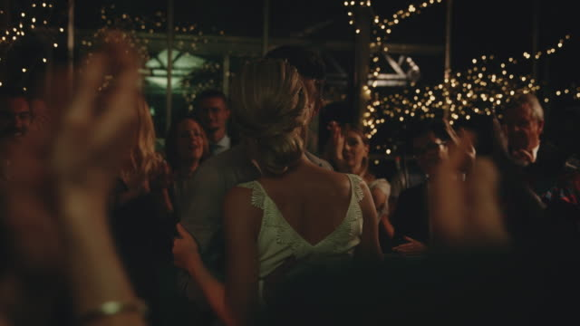 guests clapping for newlyweds dancing at wedding - young couple wedding friends video stock e b–roll