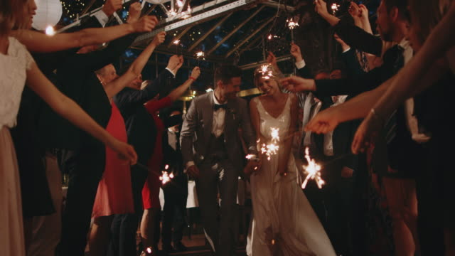 Guests holding sparklers over running newlyweds Male and female guests holding sparklers while standing in row. Bride and bridegroom running along while holding hands. They are in wedding ceremony at night. newlywed stock videos & royalty-free footage