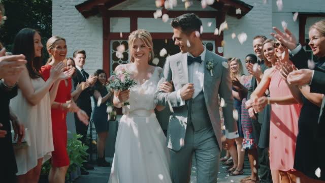 vídeos y material grabado en eventos de stock de invitados lanzando pétalos sobre pareja saliendo de la iglesia - novio relación humana
