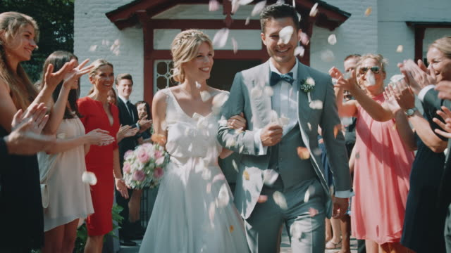 guests throwing petals over couple outside church - matrimonio video stock e b–roll