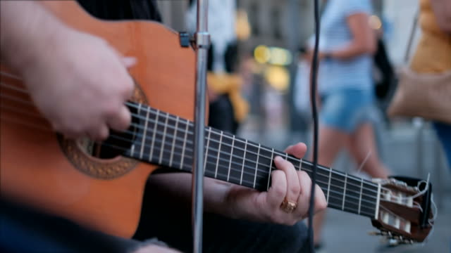 Guitar And Male Fingers Of Street Artist On Musical Instrument Young man playing guitar and singing song on sidewalk. Street artist with musical instrument in Madrid, Spain, Europe. Singer, music and arts. Close-up of strings and fingers performer stock videos & royalty-free footage