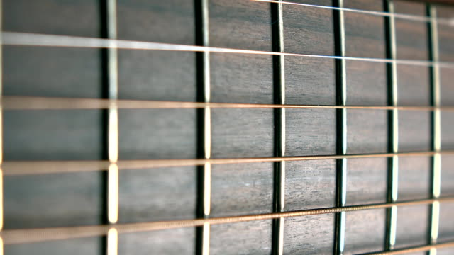 Guitar fret and six strings, shallow focus. Music performance. FullHD macro dolly shot video