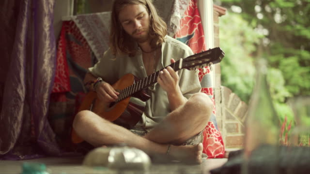 Guitar Hippie Stock video clip of a male hippie, sitting cross-legged by an open door playing the guitar. guitar stock videos & royalty-free footage