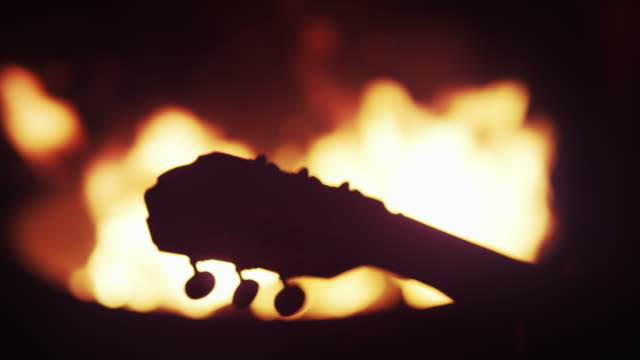 guitar neck silhouetted at bonfire - falò spiaggia video stock e b–roll