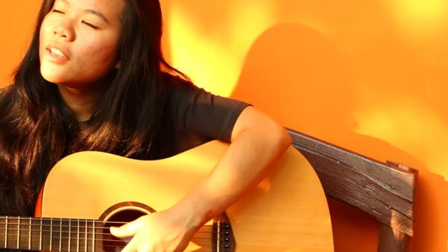 vídeos y material grabado en eventos de stock de joven mujer tocando la guitarra - ojo morado