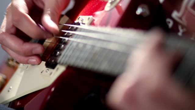 Guitarist hand strumming at electric guitar string video