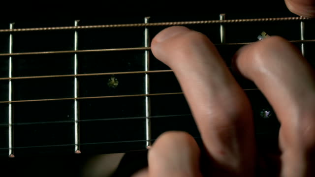 Guitarist hand touching strings on fretboard. Music performance. FullHD macro video video
