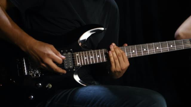 gitarrist i svart skjorta sitter på en stol som utför sång i mörkt rum - gitarrist bildbanksvideor och videomaterial från bakom kulisserna
