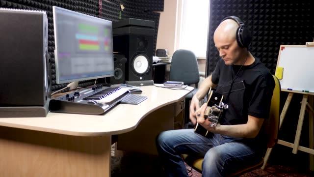 Guitarist In Headphones Records Instrumental Audiotrack In Studio