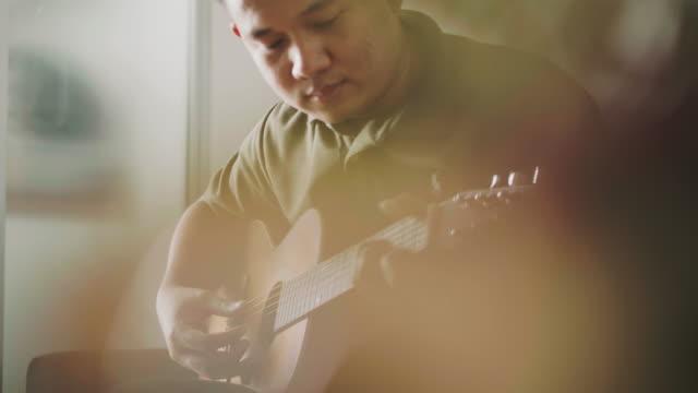 stockvideo's en b-roll-footage met gitarist is het spelen van gitaar tijdens het gebruik van capo - 25 29 jaar