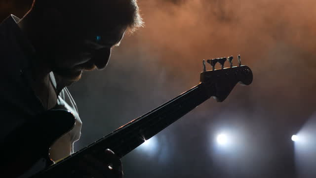 Guitarist on stage, musician tunes his instrument before the concert.