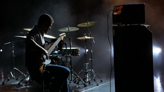 Guitarist playing bass guitar live on stage in rays of light.