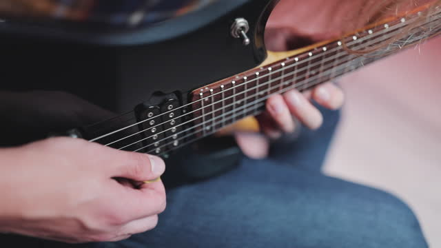 A guitarist plays a rock riff with his guitar. Professional Guitarist Playing Riffs On Electric Guitar At Home Studio
