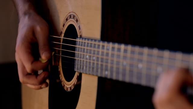 gitarristen spelar ackord på akustisk gitarr hemma - akustisk gitarr bildbanksvideor och videomaterial från bakom kulisserna