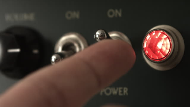 vídeos de stock e filmes b-roll de guitarist powering on vintage tube guitar amplifier - músico