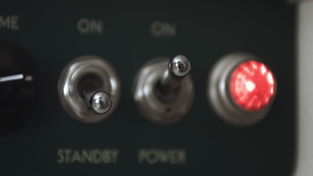Guitarist Switching On Tube Amplifier And Red Light Indicator Is On