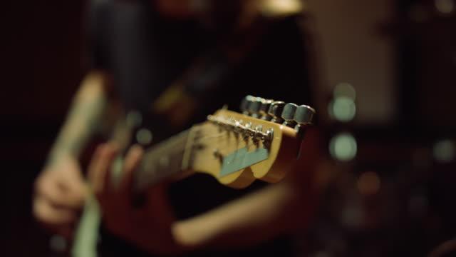 gitarristen vänder rattar på greppbräda i studio. man som håller gitarr i hall. - akustisk gitarr bildbanksvideor och videomaterial från bakom kulisserna