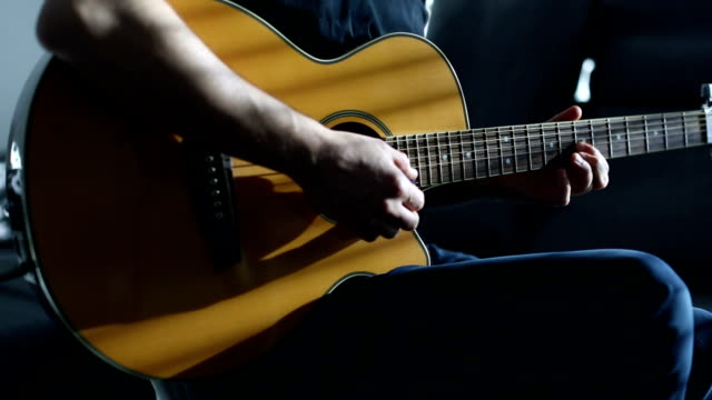 Guitarst playing acoustic guitar Guitarst playing acoustic guitar side lit stock videos & royalty-free footage