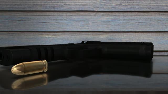 A gun and bullet on a glass table selective focus