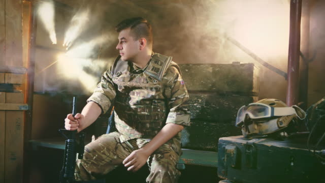Gun in hand. Man in uniform. Military man. People in war. Soldier in army 4k. Man in uniform with a flag on clothes. Person with gun in hand. Military human with a beautiful haircut. Sunlight from shot holes in the wall. People in the war. Serious army soldier. Slow motion 4k. us military stock videos & royalty-free footage