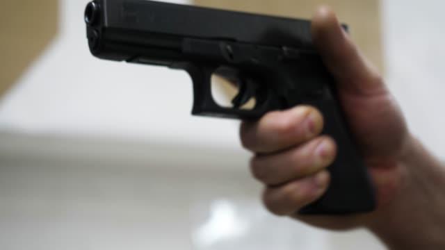 gun in the man's hand. man holding a gun close-up. black handgun in hand of a man - giuntura umana video stock e b–roll