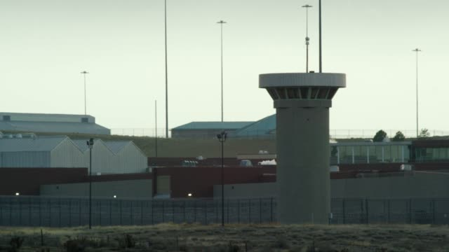 """gun towers and the exterior of the united states penitentiary, administrative maximum facility supermax prison complex in florence, colorado (fremont county) under the rocky mountains - the """"alcatraz of the rockies"""" - prigione video stock e b–roll"""