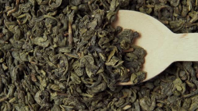 gunpowder grüner chinesischer tee aus nächster nähe. hölzerne dessert löffel schöpfe getrocknetgerollte blätter - grüner tee stock-videos und b-roll-filmmaterial