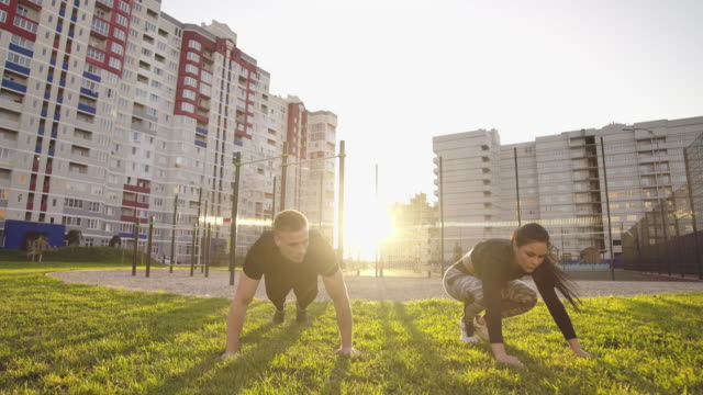 guy and girl push-ups outdoors. male and female doing exercises together outdoor. couple doing sport keeping the body in tension, leaning on the extended arms. - man city exercise abs video stock e b–roll