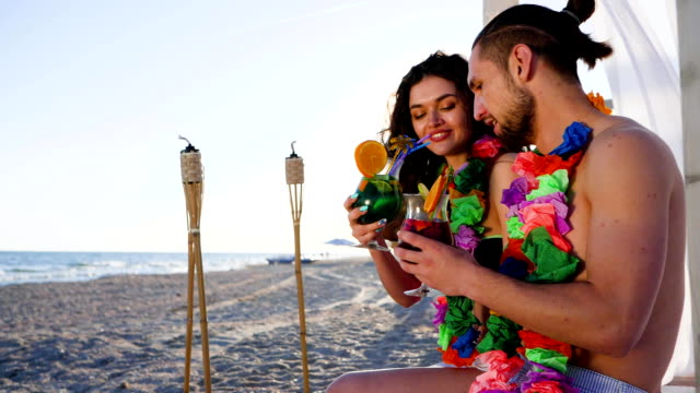 guy and girl to exotic vacation to Hawaiian Islands, happy friends drink cocktail in ocean coast video
