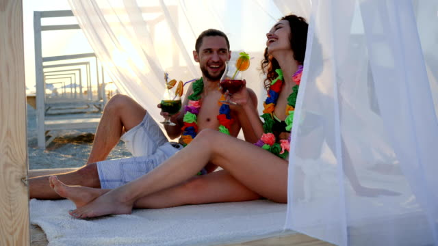 guy and girlfriend with colorful wreaths, backlight, couple drink cocktails, summer season, wind develops white cloth at bungalow video
