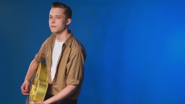 Guy appears and leaves frame playing guitar, on blue background video