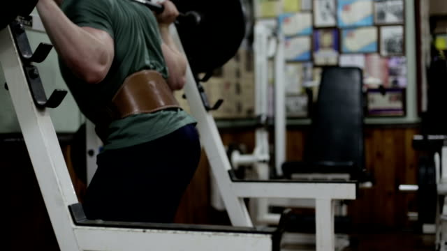 Guy crouches with a barbell The guy crouches with a barbell in the gym. short length stock videos & royalty-free footage