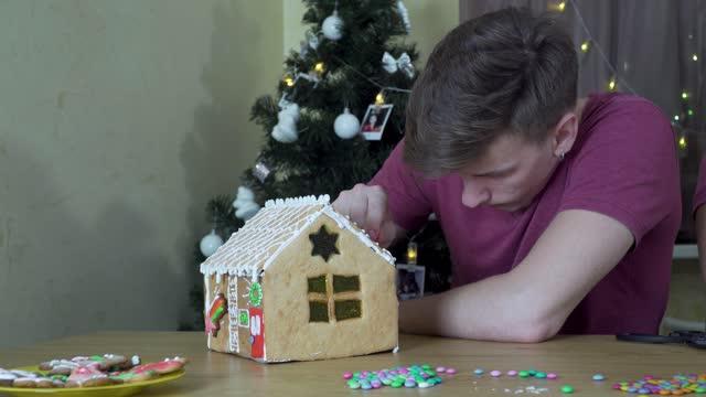 ein kerl schmückt ein weihnachts-lebkuchenhaus - lebkuchenhaus stock-videos und b-roll-filmmaterial