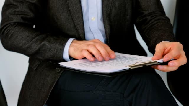 vídeos de stock e filmes b-roll de guy documents job applicant skimming papers cv - dossier