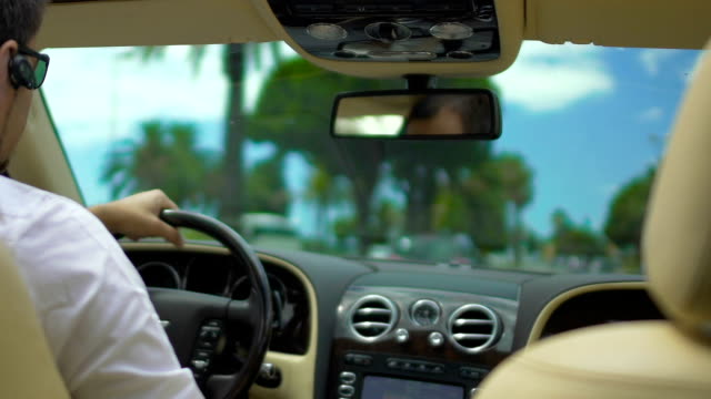 Guy driving expensive car down road with palm trees, business driver, service Guy driving expensive car down road with palm trees, business driver, service luxury car stock videos & royalty-free footage