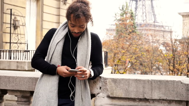 Mulatto guy enjoying smartphone and earphones with Eiffel tower in background in slow motion video